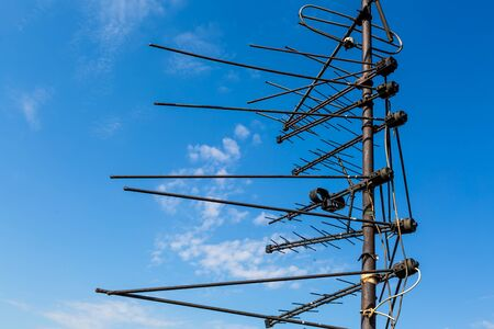 TV antennas are on the mast and blue sky as a background