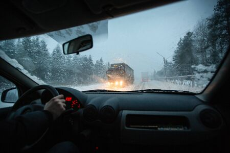 Man drives a car on the winter winter speedway in a snow storm in the twilight when snow with rain is flying. Concept of driving in the dangerous conditions with bad visibility on the winter.