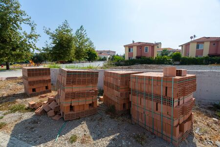 Construction Materials. Building materials for construction of residential complex. Pile of red bricks and scattered bricks at construction site.