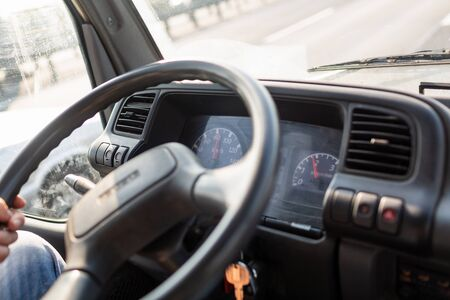 Male driving a truck and holding steering wheel of truck during the movement in the road. Image with selective focus on the wheel, dashboard with speedometer and tachometer, blurred windshield