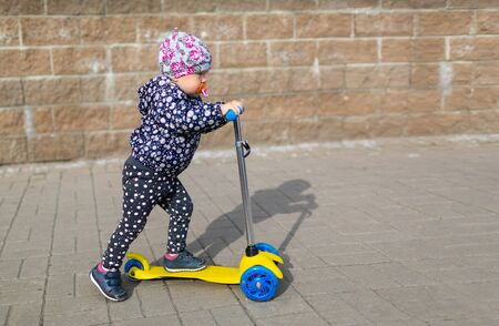 Little beautiful baby girl with pacifier is riding on the childish scooter outdoors. Concept of children activity and kid sport.