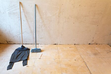 House cleaning equipment such as a mop with rag in apartment that is under construction, remodeling, renovation, overhaul, extension, restoration and reconstruction. Concept of home cleaning.
