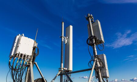 Telecommunication masts with microwave, radio panel antennas, outdoor remote radio units, power cables, coaxial cables, optic fibers are installed on the top mast and blue sky as background.