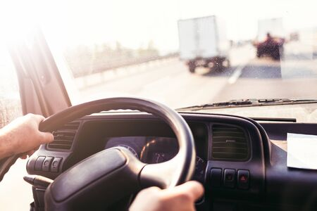 Male driving a truck and holding steering wheel of truck or lorry during the movement in the road. Image with selective focus on the wheel, dashboard with speedometer and tachometer, blurred windshiel