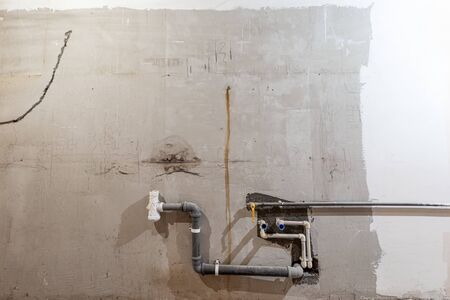 Plastic tubes of plumbing and canalization in apartment that is under construction, remodeling, renovation, overhaul, extension, restoration and reconstruction. Concept of total home improvement.
