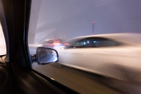 Image with motion blurred effect.Cars fast drive on the winter speedway or highway with roadway lighting in a snow storm in the twilight when snow with rain is flying. Concept of driving in the dangerous conditions with bad visibility on the winte 写真素材 - 135555929