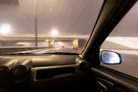 Image with motion blurred effect.Cars fast drive on the winter speedway or highway with roadway lighting in a snow storm in the twilight when snow with rain is flying. Concept of driving in the danger