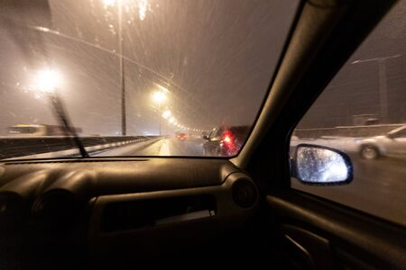 Image with motion blurred effect.Cars fast drive on the winter speedway or highway with roadway lighting in a snow storm in the twilight when snow with rain is flying. Concept of driving in the dangerous conditions with bad visibility on the winte 写真素材 - 135556315