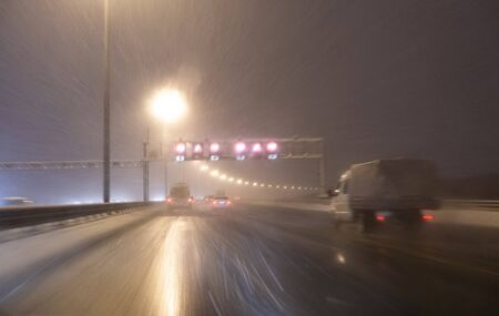 Image with motion blurred effect.Cars fast drive on the winter speedway or highway with roadway lighting in a snow storm in the twilight when snow with rain is flying. Concept of driving in the dangerous conditions with bad visibility on the winte 写真素材 - 135557115