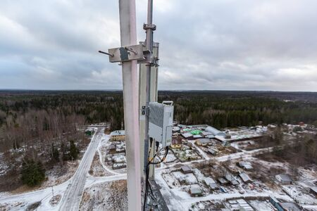 Top of red telecommunication tower with vertical panel antenna and remote radio unit, power and optic cables in winter day. 写真素材 - 137151951