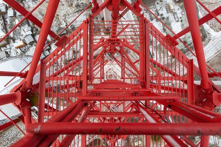 Red telecommunication tower or mast with microwave, radio panel antennas, outdoor remote radio units, power cables, coaxial cables, optic fibers are on the top mast that located in forest . View from top to down of tower. 写真素材 - 137151952