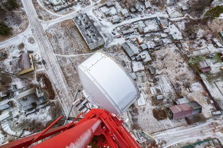 Red telecommunication tower or mast with microwave, radio panel antennas, outdoor remote radio units, power cables, coaxial cables, optic fibers are on the top mast that located in forest . View from top to down of tower. 写真素材 - 137151953