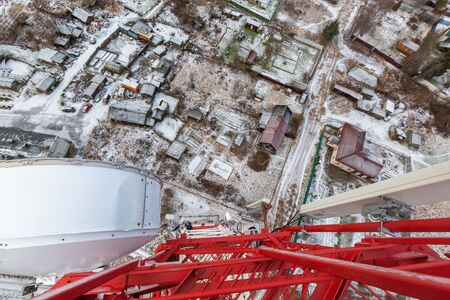 Red telecommunication tower or mast with microwave, radio panel antennas, outdoor remote radio units, power cables, coaxial cables, optic fibers are on the top mast that located in forest . View from top to down of tower. 写真素材 - 137151954