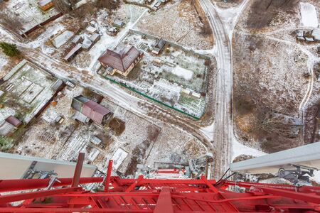 Red telecommunication tower or mast with microwave, radio panel antennas, outdoor remote radio units, power cables, coaxial cables, optic fibers are on the top and ground road and is as background. Vi 写真素材