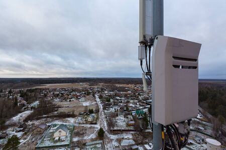 Top of red telecommunication tower with vertical panel antenna and remote radio unit, power and optic cables in winter day. 写真素材 - 137151957