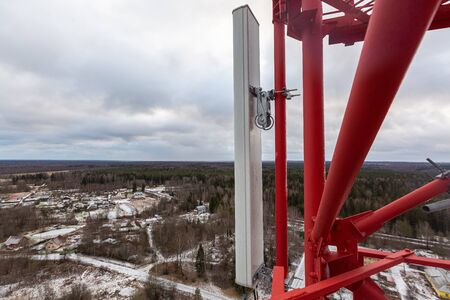 Top of red telecommunication tower with vertical panel antenna and remote radio unit, power and optic cables in winter day.