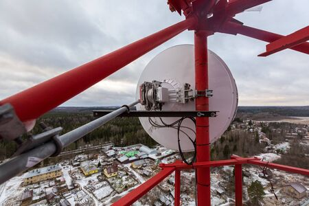 Red telecommunication tower or mast with microwave, radio panel antennas, outdoor remote radio units, power cables, coaxial cables, optic fibers are on the top mast that located in forest . View from  写真素材