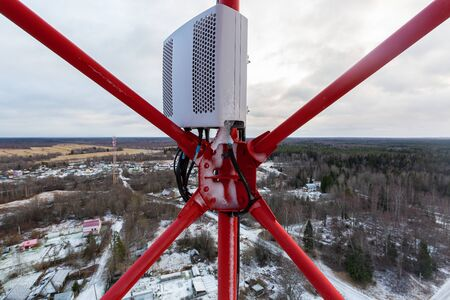 Red telecommunication tower or mast and remote electric tilt and remote radio unit with power and optic cables in winter day 写真素材 - 137151974
