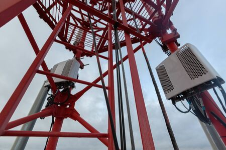 Red telecommunication tower or mast with vertical panel antenna, remote electric tilt and remote radio units, power and optic cables in winter day 写真素材