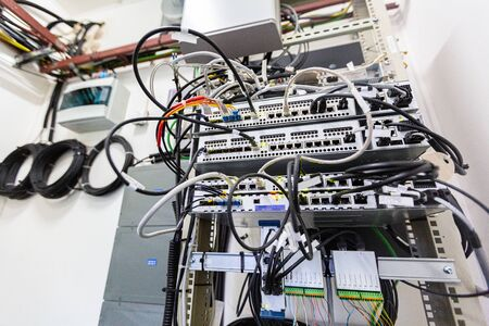 Inside of typical modern basic station of communications equipment and bights of optic cables or fibers on the wall