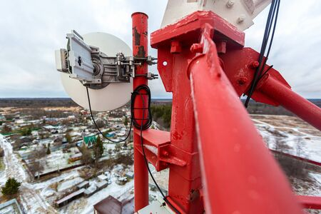 Red telecommunication tower with antenna and installed radio microwave equipment with coaxial cabel for transmitting data to other mobile basic station 写真素材 - 137151980