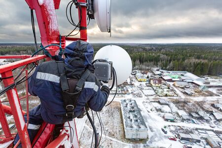 Professional industrial climber in uniform and climber equipment on the telecommunication tower is installing outdoor unit to antenna for next adjustment. Working process of upgrading telecommunicatio 写真素材