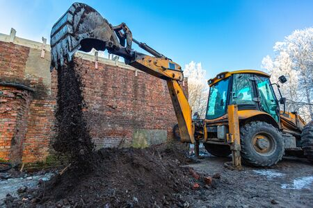 The modern excavator performs excavation work on the construction site. Front view of a digger bucket of digging ground as a part of industry machinery