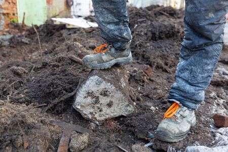Worker in dirty uniform and shoes with orange laces is staying in the stone in construction site. Concept of diry and hard work during construction, remodeling, renovation, extension, overhaul, restor