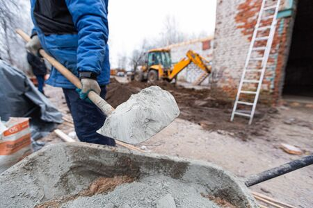 Worker in protect gloves is loading the cement by shovel to building trolley with sand to making the concrete in construction site. Concept of using of construction materials during construction, remo