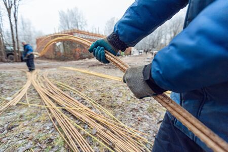 Workers in protect gloves are holding light polymer reinforcement in construction site. Concept of using of light construction materials during construction, remodeling, renovation, extension, overhau