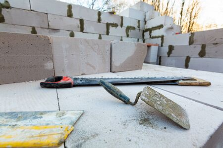 Trowel, a couple of saws are on the foamed concrete block during the building house on the construction site 写真素材