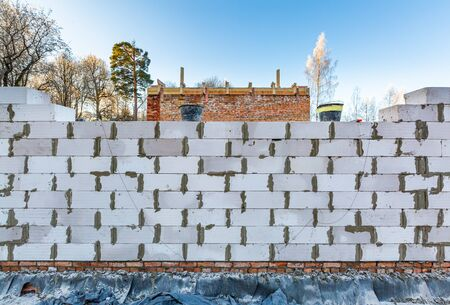 Unfinished wall made from foamed concrete block during the building house on the construction site. 写真素材