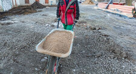Worker in protect gloves is hauling the building trolley with sand to making the concrete in construction site. Concept of using of construction materials during construction, remodeling, renovation,  写真素材
