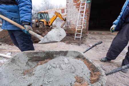 Trabajador en guantes de protección está cargando el cemento con una pala al carro de construcción con arena para hacer el concreto en el sitio de construcción. Concepto de uso de materiales de construcción durante la construcción, remodelación, renovación, ampliación, revisión, restauración y reconstrucción.