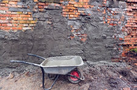 Bilding trolley with concrete in construction site and brick wall with concrete places . Concept of using of construction materials during construction, remodeling, renovation, extension, overhaul, re