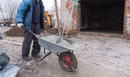 Worker in protect gloves is holding the building trolley with sand to making the concrete in construction site. Concept of using of construction materials during construction, remodeling, renovation,