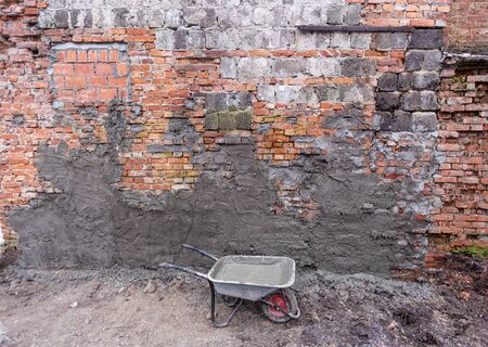 Bilding trolley with concrete in construction site and brick wall with concrete places . Concept of using of construction materials during construction, remodeling, renovation, extension, overhaul, restoration and reconstruction Stockfoto
