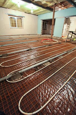 Pipefitter installing system of heating or underfloor heating installation. Water floor heating system interior. Plumbing pipes in apartment during under construction, remodeling, renovation, extension, restoration, reconstruction, upgrade