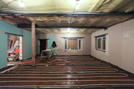 Pipefitter installing system of heating or underfloor heating installation. Water floor heating system interior. Plumbing pipes in apartment during under construction, remodeling, renovation, extensio 写真素材
