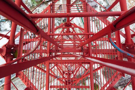 Red telecommunication tower or mast with microwave, radio panel antennas, outdoor remote radio units, power cables, coaxial cables, optic fibers are on the top mast. View from top to down of tower. 写真素材