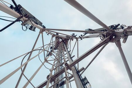 Telecommunication tower with vertical panel antenna and remote radio unit, power and optic cables and sky 写真素材