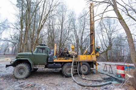 Hydraulic ground water hole drilling machine installed on the old truck with big wheels on the construction site. Groundwater well drilling