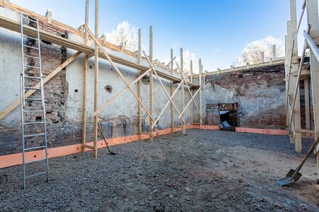 Process of solidification of concrete floor before pouring and reinforcement of load-bearing walls with wooden beams on the construction site. 写真素材