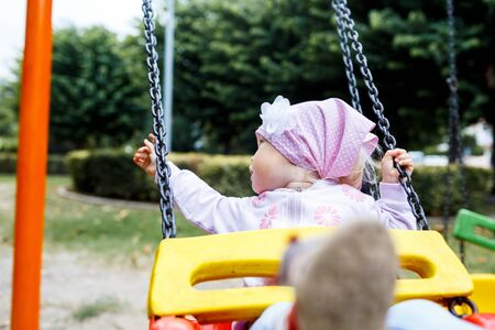 Adorable smiling baby girl with kerchief enjoying a swing ride on a playground in a park on a nice sunny summer day. 写真素材