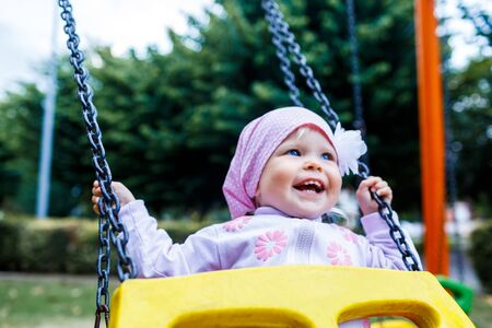 Adorable smiling baby girl with kerchief enjoying a swing ride on a playground in a park on a nice sunny summer day 写真素材