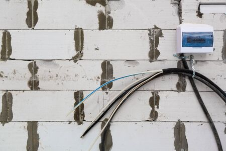 Image with focus view on the electrical power cables fixed on the wall made from foamed concrete block during the building house on the construction site. Cable prepared to installing to electrical bo