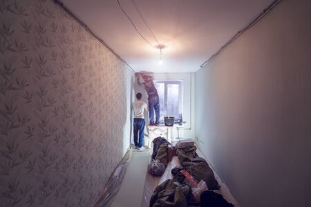 Workers are paperhanging in apartment that is under construction, remodeling, renovation, extension, restoration and reconstruction. Concept of home improvement