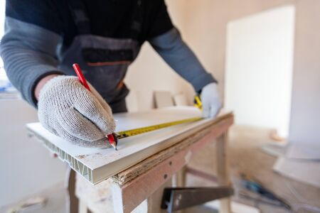 Worker is measuring plastic detail with pencil and tape-line before cutting in apartment that is under construction, remodeling, renovation, overhaul, extension, restoration and reconstruction. Concept of total home improvement.