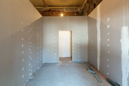 Working process of installing metal frames for plasterboard or drywall for making gypsum walls in apartment is under construction, remodeling, renovation, extension, restoration and reconstruction. Standard-Bild