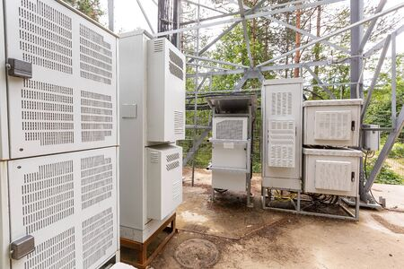 Climatic vandal-proof cabinets with microwave equipment and power cables, coaxial cables, optic fibers are installed near the mast in rural. Typical basic station of telecommunication operators.